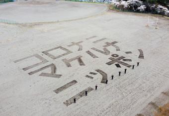 久慈工高の校庭に描かれた「コロナニマケルナニッポン」の文字(同校提供)