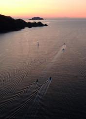 待望のウニ漁解禁。朝焼けの中、小舟が連なって漁場へと向かう=釜石市・両石湾(本社小型無人機から撮影)