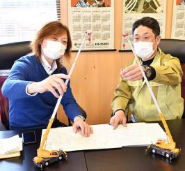 移動式クレーン車2台を使ってこいのぼりを掲揚する打ち合わせをする松本龍太さん(左)と佐々克考さん。地元の子どもたちに自宅や車窓から眺めてもらう