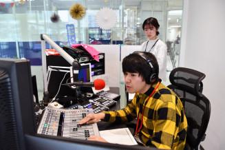 コロナ禍に立ち向かう経営者の工夫や思いを電話中継するパーソナリティーの阿部直大さん(手前)と阿部満穂子さん