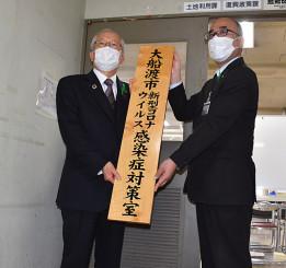 対策室の看板を設置する戸田公明市長(左)と佐々木義久室長