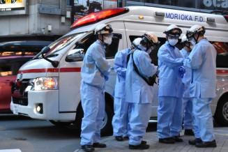 新型コロナウイルス感染症対策の装備で駆け付けた救急隊員=3日午後6時16分、盛岡市大通