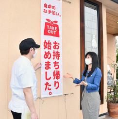 「地元の飲食店を応援したい」とのぼり旗を寄贈する伊藤純子社長(右)