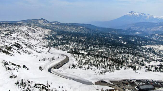 雪の回廊が続く八幡平アスピーテライン。右奥には岩手山がそびえ立つ=八幡平市・八幡平山頂付近(本社小型無人機から撮影)