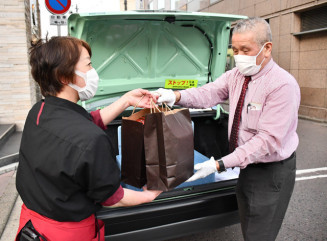 宅配する焼肉弁当を受け取る平和・とりょうタクシーの乗務員(右)。県内に新たなデリバリーの形が広がっている=8日、盛岡市盛岡駅前通