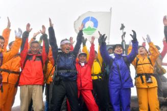 荒天で山頂式典は中止となったが、有志が登頂成功を祝って万歳で互いをたたえた岩手山の山開き=2019年7月