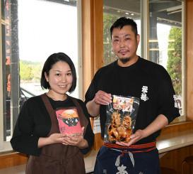 インターネットで販売予定のジャンボ焼き鳥とモツ煮をPRする喜良彦代表(右)と妻の有美さん