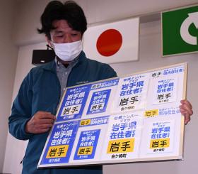 他県ナンバーでも県内在住者であることを示すシートを披露する桐山昭夫社長