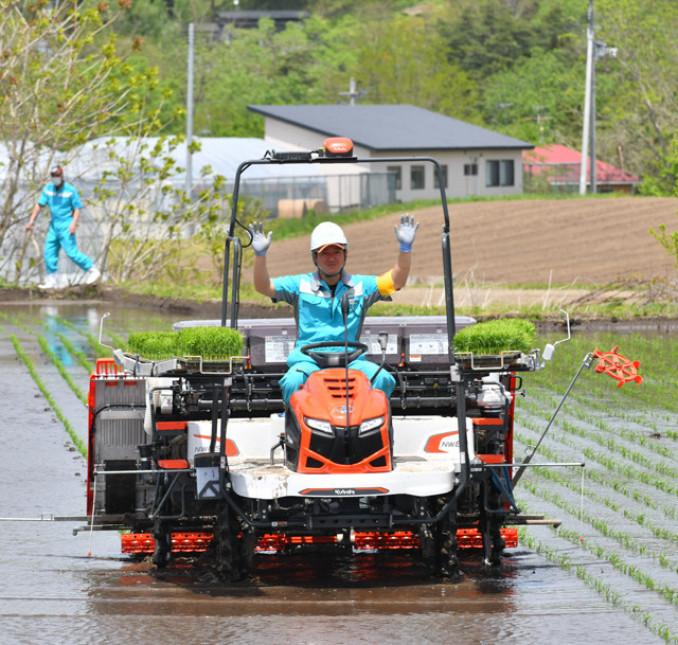 先端技術を搭載した自動の田植え機で酒米「ぎんおとめ」を植える関係者