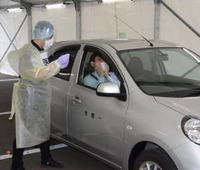臨時診療所の運営リハーサルで検体採取に当たる一関市職員=16日、同市内