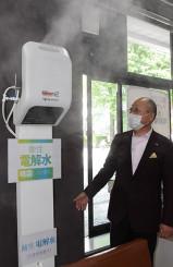盛岡市役所の市民登録課で稼働を始めた噴霧器を紹介する田口敬芳代表