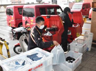 全戸向け布マスクの配達に向けて荷造りする郵便局員=23日、盛岡市中央通・盛岡中央郵便局