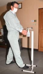 小冨士製作所が開発した「コロナカットシャワー」。足でペダルを踏むと消毒液が噴射される