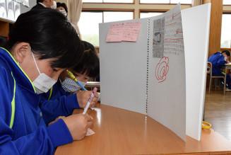 朝学習で同級生が選んだ記事を読み、感想を書き込む仁左平小6年の児童