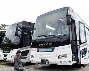 大型バスの安全点検を行うリアス観光の社員。苦境の中、再び安心して観光が楽しめる日を信じて準備を重ねる=27日、宮古市根市