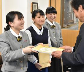 松橋文明学園長(右)に絵本を手渡す(左から)佐々木結菜さん、土沢葵さん、藤社彩乃さん