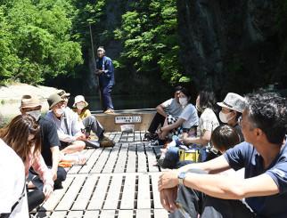 まぶしい新緑の風景を楽しむ舟下りの観光客