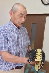 大谷翔平のサイン入りグラブを見つめ、少年期の思い出を振り返る浅利昭治さん