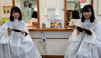 ヘアドネーションのためカットした髪を手にする千田彩梨さん(右)と佐々木草耶さん