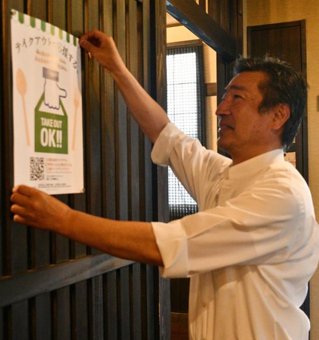 久慈テイクアウトのポスターを店に張る橋本勝文さん