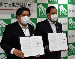 中心市街地の活性化に向けた連携協定を結んだ谷藤裕明市長(右)と石田亨支社長