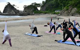 朝の普代浜で伸び伸びと体を動かす参加者