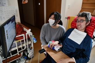 オペレートナビを操作する郷家準一さん(右)と妻の知洸さん。パソコンや文字盤も併用し、コミュニケーションを図る