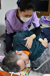 奥州市水沢の自宅で、作業療法士から呼吸補助のリハビリを受ける郷家準一さん(下)。誤嚥を起こしやすい病状を踏まえ、唾液やたんをはき出させるような療法も施されている