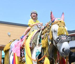 馬コに乗って笑顔を見せる園児