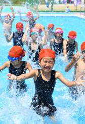 水しぶきを上げ、待望のプール開きを喜ぶ萩荘小の児童=10日、一関市萩荘
