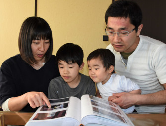 アルバムで家族の思い出を振り返る小谷地さん一家。朋美さん(左)は、震災時に爽多君(左から2人目)を助けてくれた女性へ感謝の思いを募らせる