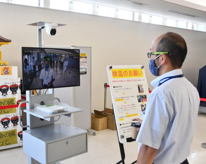 花巻空港の国内線搭乗口に設置されたサーモグラフィーカメラで検温する県職員