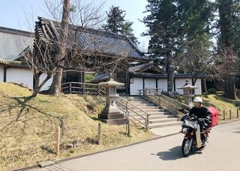 中尊寺本堂正面の参道をバイクで走る配達員。周囲の状況に合わせ、安全に配慮して通行する