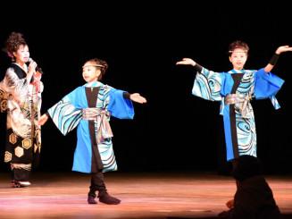 伸びやかな歌声を披露する小田代直子さん(左)と、愛らしく踊る八重樫しおりさん(右)、みさきさん姉妹