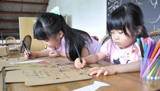 父の日ギフトの箱やカードに、カラフルな絵とメッセージを描く子どもたち