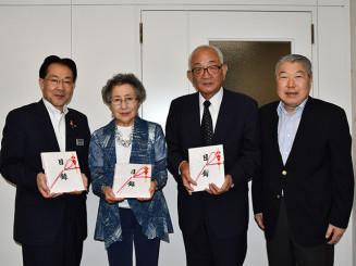 玉山哲会長(右)から寄付を受け取った3団体の代表者