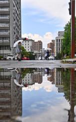 雨で道路に水がたまり、鏡となって街が映り込んだ=16日、盛岡市内丸(報道部・山本毅撮影)