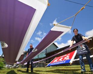 青空の下、染め物のはんてんや大漁旗を天日干しする職人=17日、花巻市藤沢町・伊藤染工場