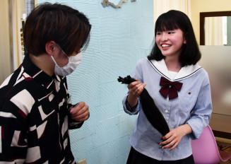 カットした髪を手に取る小原美香さん(右)