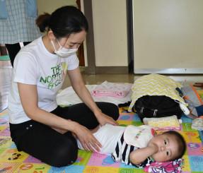 徳田真理子さんの指導で、赤ちゃんにマッサージをする参加者