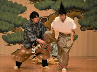 「文相撲」で秘伝の書を手に相撲を取る大名役を演じる野村萬斎さん(右)