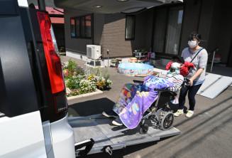 知洸さん(右)に押され、車椅子のまま車に乗り込む郷家準一さん。外出時は紫色のディズニータオルを掛けるスタイルがお気に入りだ=奥州市水沢