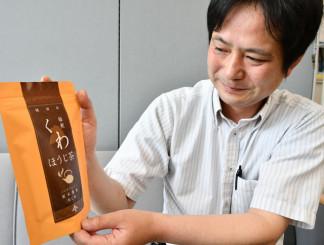 更木桑茶シリーズの新商品「くわほうじ茶」を手にする福盛田洋幸社長
