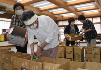 食品の箱詰め作業に励む参加者。住民らの善意をひとり親世帯に届ける