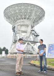 ブラックホールの研究に使うアンテナの前に立つ本間希樹所長(左)=1日、奥州市水沢・水沢VLBI観測所