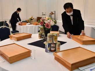 弁当や缶ビールを並べて宴会の準備をするスタッフ。ホテルなどは安全安心を前面に出した「新しい宴会」を提案する=盛岡市・ホテルニューカリーナ