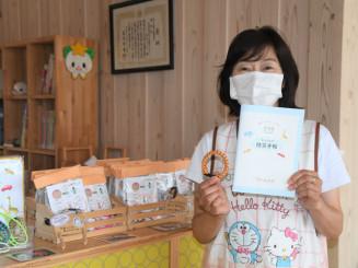 冊子とパラコードブレスレットを手に「災害に日頃から備えて」と呼び掛ける伊藤昌子代表理事