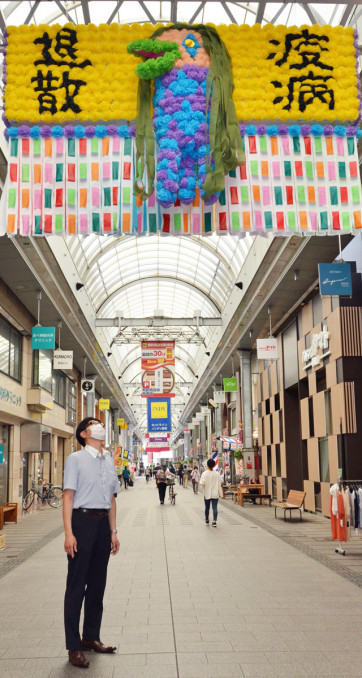 肴町商店街のアーケードでアマビエの七夕飾りを見上げる通行人