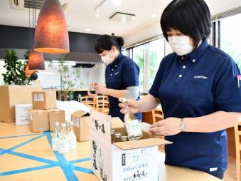 県内で製造されたアルコール消毒液を箱詰めする北良の従業員。熊本県の豪雨被災地の感染症対策を支援する=6日、北上市