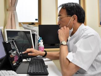 タブレット端末を前にオンライン診療の作業を確認する岩井直路所長。コロナ禍での安心確保だけでなく、災害時にも備える